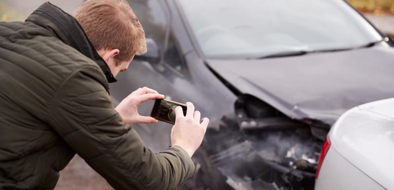 This image shows a man taking photo documentation of a car accident in Lebanon, OH
