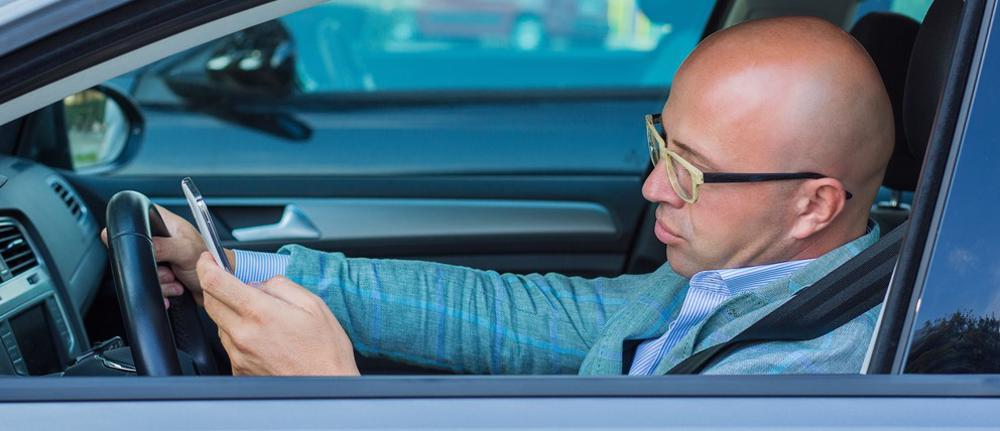 This image shows a man texting while driving in Cincinnati, OH