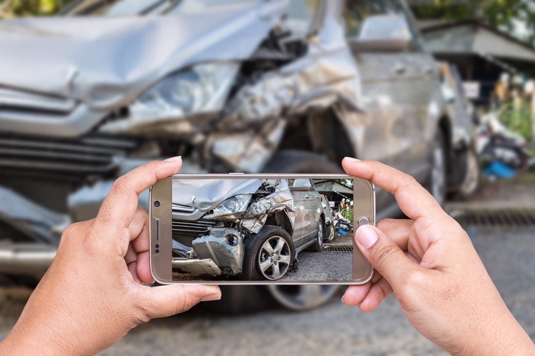 A man documenting the scene of a car accident in Centerville, OH.