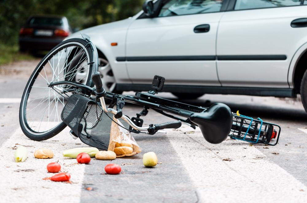 This image shows a bicycle lying on the ground after being struck by a vehicle that failed to yield at a pedestrian crossing.