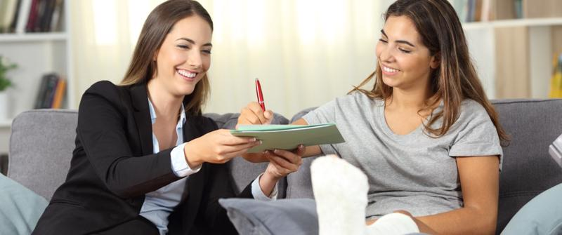 This image shows an injured client happily signing her settlement with her Finneytown personal injury lawyer.