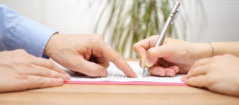 This image shows a client signing their documents with a Hamilton personal injury lawyer.