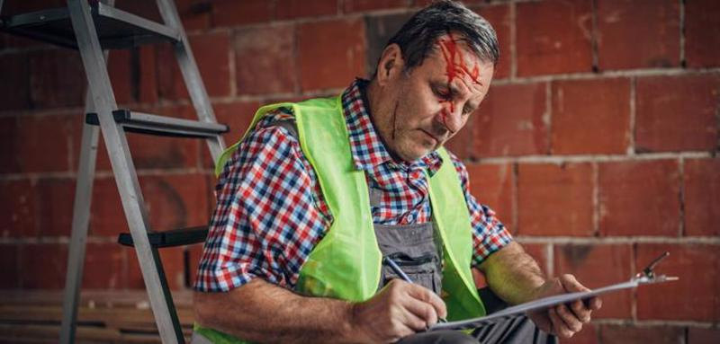 A man with a head injury filling out a Workers' Compensation form.