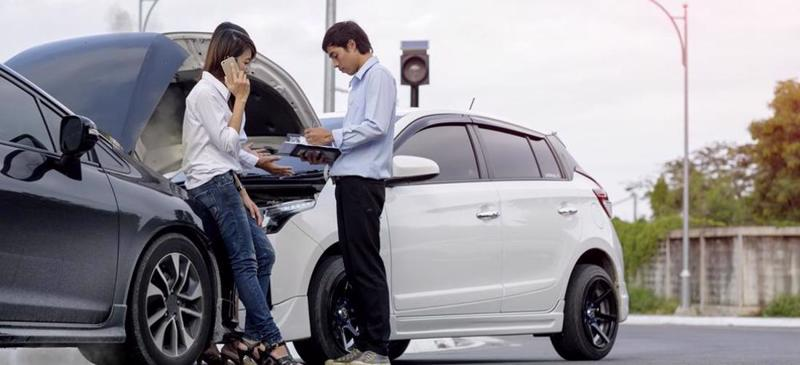 A woman on the phone and a man taking notes after a car accident.