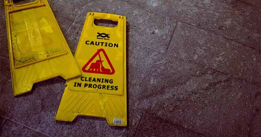This image shows a slip-and-fall sign in a busy lobby.